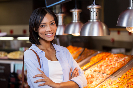 Happy woman standing with arms crossed at food counter in supermarket