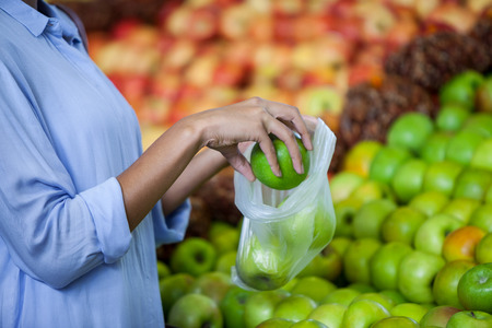 Mid section of woman buying an apple in supermarket Stock Photo