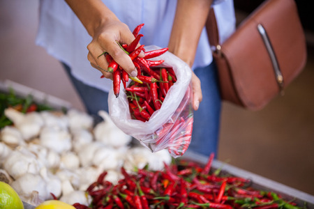 Mid section of woman buying red chilies in supermarket