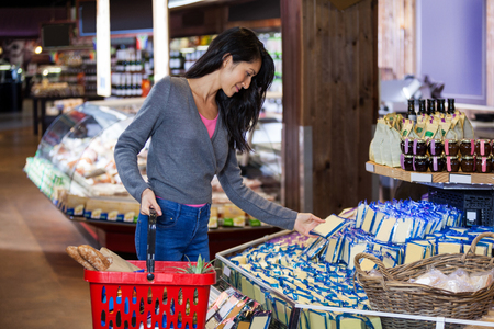 Woman selecting dairy products in grocery section of supermarket