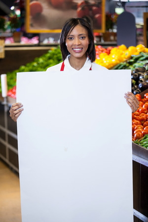 Portrait of female staff holding blank sheet in organic section of supermarket