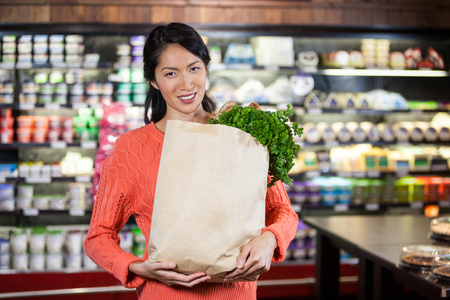 grocery bag: Portrait of woman holding groceries in grocery bag of supermarket Stock Photo