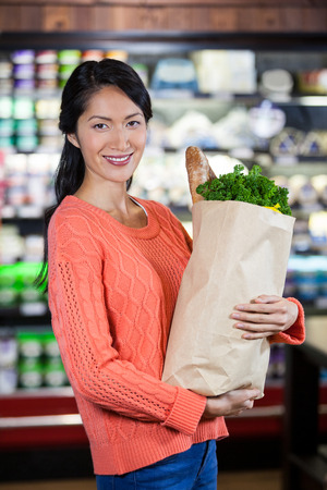 Portrait of woman holding groceries in grocery bag of supermarket Stock Photo