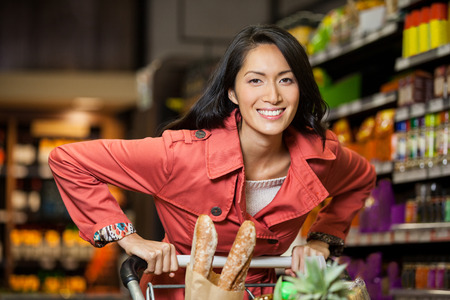 Woman holding shopping cart in organic section of supermarket
