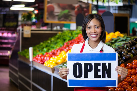 store sign: Portrait of smiling female staff holding open signboard in organic section of supermarket Stock Photo