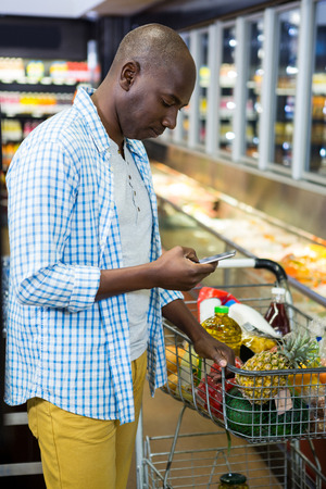 Man using mobile phone in grocery section while shopping at supermarket