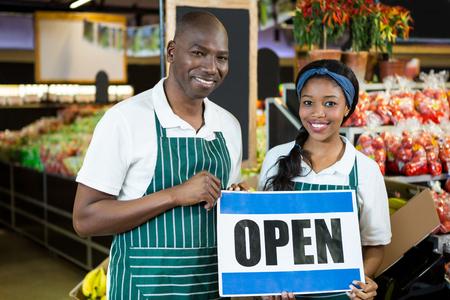 Portret van glimlachend personeel die open tekenraad in organische sectie van supermarkt houden