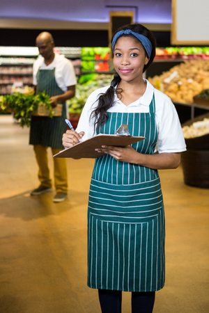 Portrait of female staff writing on notepad in super market Stock Photo