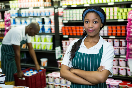 mani incrociate: Portrait of female staff standing with hands crossed in supermarket