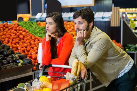berenjena: Pares agujereados con carrito de la compra en la sección orgánica de supermercado Foto de archivo