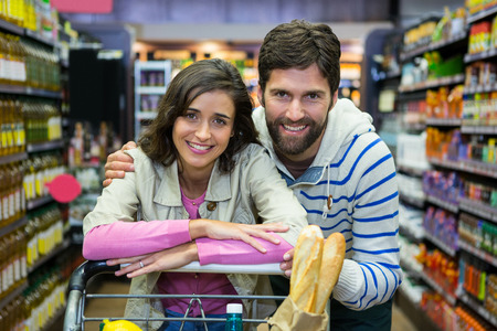 business relationship: Portrait of happy couple leaning on trolley at supermarket