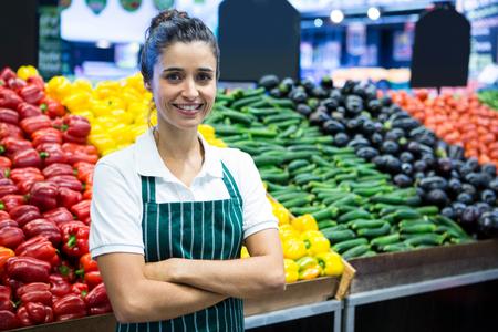 berenjena: Retrato del personal femenino que se coloca con el brazo cruzado en la sección orgánica del supermercado