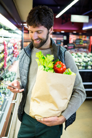 grocery bag: Man using mobile phone while holding grocery bag in supermarket