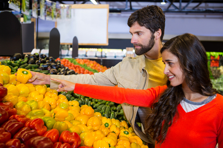 Couple buying vegetables in organic shop at super market