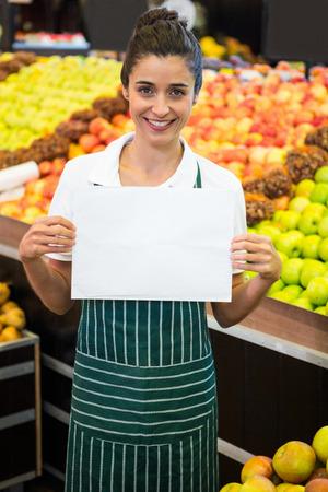 hoja en blanco: Retrato de la sonrisa de personal femenino que sostiene una hoja en blanco en el supermercado