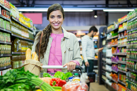 Portrait of smiling woman with vegetables in shopping trolley at supermarket