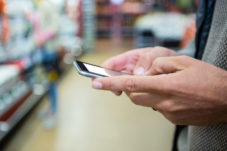 Hands of man using mobile phone at supermarket