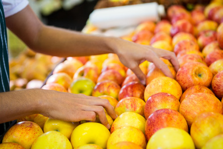 Female staff arranging fruits in organic section of supermarket