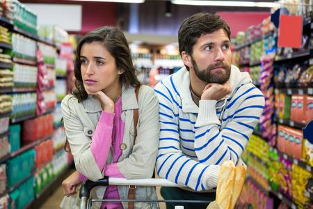 슈퍼마켓의 유기 부분에서 쇼핑 트롤리와 지루한 부부