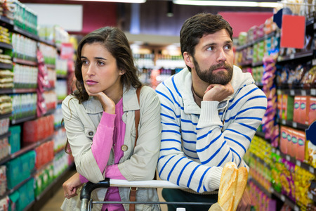 Bored couple with shopping trolley in organic section of supermarket Stock fotó