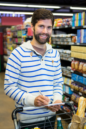 Portrait of man writing on notepad while shopping in grocery section at supermarket Stock Photo