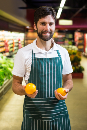 Portrait of smiling male staff holding fruit in organic section of supermarket