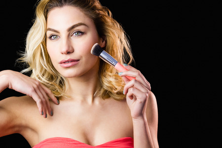 off shoulder: Close-up of beautiful woman posing with make-up brush against black background