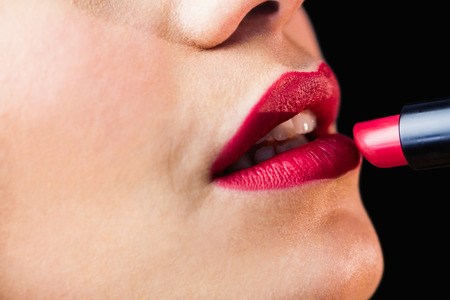 Close-up of beautiful woman applying red lipstick on lips against black background