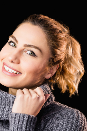 black sweater: Close-up of beautiful woman posing against black background Stock Photo