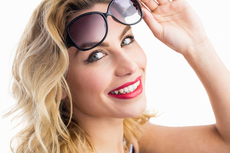 Close-up of beautiful woman posing with sunglasses against white background Stock Photo