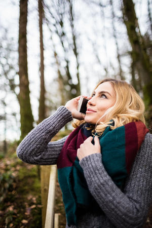 Close-up of beautiful woman talking on mobile phone in forest