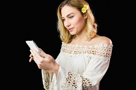 off shoulder: Beautiful woman using mobile phone against black background Stock Photo