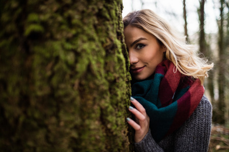woman hiding: Portrait of beautiful woman hiding behind tree trunk in forest Stock Photo