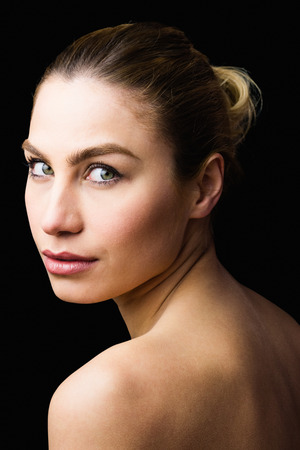 Close-up of beautiful woman posing against black background Stock Photo