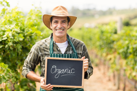 Portrait of a smiling farmer holding an organic sign Stock Photo