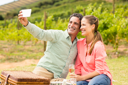 Happy couple taking a selfie in vineyard Stock Photo