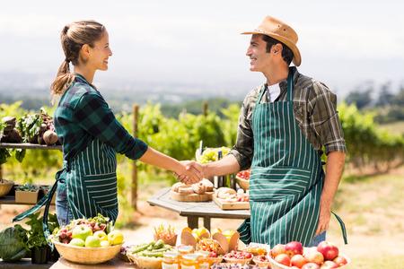 地元の市場でお互い握手農家夫婦