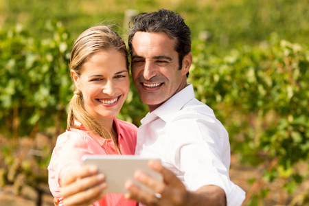 tomando refresco: Happy couple taking a selfie in vineyard Foto de archivo