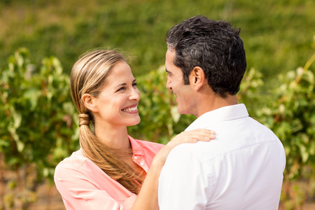 each other: Happy couple embracing each other in vineyard Stock Photo