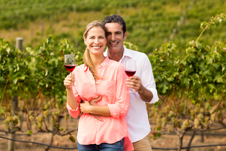 Portrait of happy couple holding glasses of wine in vineyard Stock Photo