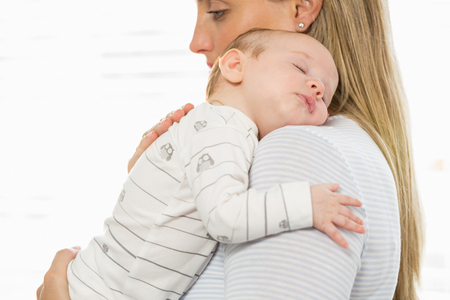 domicile: Mother holding and embracing her baby boy at home Stock Photo