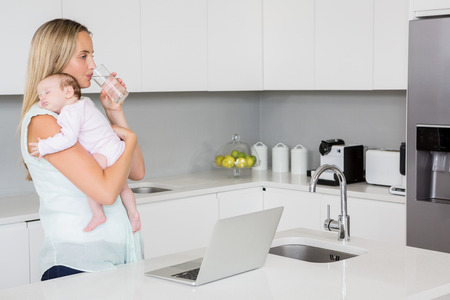 Mother drinking water while carrying baby in kitchen at home Stockfoto