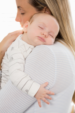 Mother holding and embracing her baby boy at home Stock Photo