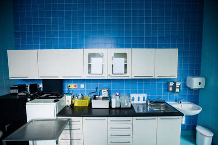 cabinets: Cabinets, refrigerator, wash basin, worktop and sink in hospital room