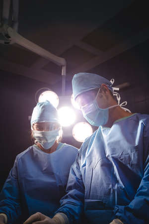 scrub cap: Surgeons performing operation in operation room at the hospital LANG_EVOIMAGES