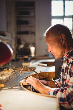 coping: Attentive goldsmith shaping metal with coping saw in workshop