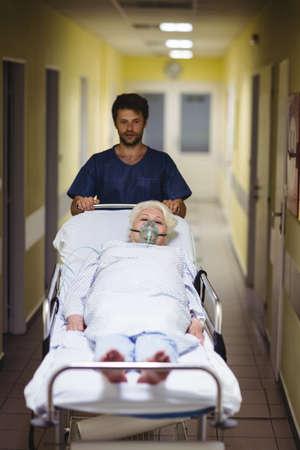 paciente en camilla: Muchacho de la sala que empuja a un paciente mayor en stretcher en el pasillo del hospital
