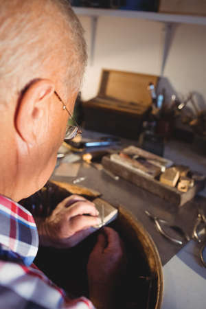 attentive: Attentive goldsmith working in workshop LANG_EVOIMAGES