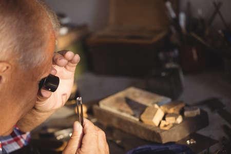 appraising: Goldsmithexamining diamond through loupe in workshop