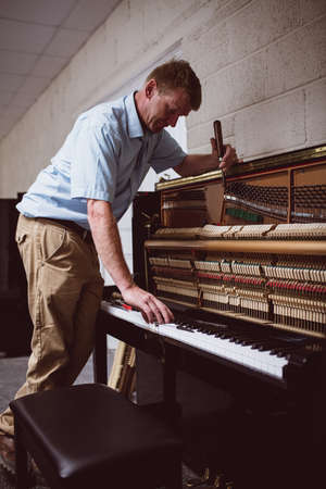 classical mechanics: Piano technician repairing the piano at workshop